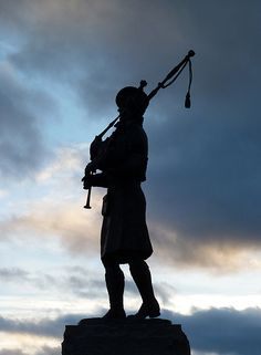 A silhouetted statue at House of Bruar by Walter Baxter.....This bagpipe playing figure stands on a granite block as a tribute to the fallen soldiers of the 51st Highland Division.