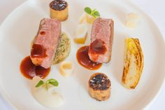 Gebakken tamme eendenborst met een strudel van zijn boutje, quinoa, gebakken witlof, gebrande hazelnoten en saus van rode wijn