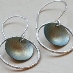Silver Hoop Earrings - Sage Green.   Made from argentium silver and heat patina titanium. The play of greens, blues and amber color of the titanium add interest and drama to this elegantly simple design by Ilene Kay.
