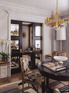 obsessed with the mod brass chandelier + agate inspired upholstery, paired with a dramatic marble table + mirrored sliding doors