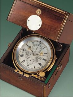Two-day marine chronometer with auxiliary compensation and 56-hour power reserve indicator. Barraud, Maker for the Royal Navy. Cornhill, London.1850. Precision Timekeeper with 1 Complication; Brass bowl with weighting ring and threaded glazed bezel gimbaled in three-body brass-bound mahogany box with glazed panel in the top under hinged lid with fitted catch. Flush-fitted brass handles and round mother-of-pearl plate, Breguet-type key in a corner plate, gimbal ring locked by two swivel arms.