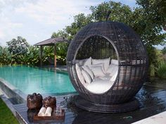 Comfy Atmosphere Canopy Bed Designs For Outdoor : Unique Black Rattan Materials Ball Shaped Canopy Bed Designs For Outdoor With Round Shaped Low Style Base Canopy On The Black Wood Flooring Also Comfortable White Fabric Matress That Have Pillows Ornament And