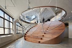 """When advertising firm Wieden+Kennedy was expanding from one floor to three, it wanted to ensure it wouldn't fragment its workplace. This sweeping """"coin"""" combines a staircase and stadium seating, visually connecting the floors."""