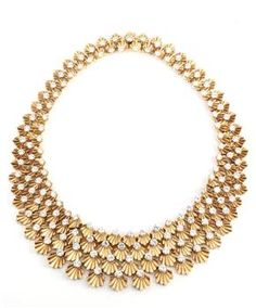 BULGARI. A HIGHLY ARTICULATED YELLOW GOLD AND DIAMOND DEMI PARURE.  Comprising a necklace and bracelet composed of palmette shaped links each accented with a brilliant-cut diamond. Made in Italy. French import marks.   Literature: Bulgari from 1884 to 2009 125 Years of Italian Jewels page 73  A similar necklace was worn by Ingrid Bergman in the film 'The Visit' of 1964