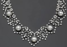 A cultured pearl, diamond and eighteen karat white gold necklace  of interlaced foliate design, suspending five graduated cultured pearls, measuring approximately 12.00 x 11.50 to 11.50 x 10.90mm., set throughout with round brilliant-cut diamonds; estimated total diamond weight: 7.90 carats; length: 16 1/4in.