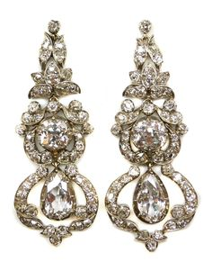 Pair of 19th century diamond pendant earrings, c.1870   , of graduated outline with a pear shaped diamond drop below a central cushion diamond, each within an openwork diamond scroll surround, foliate cluster surmount, cut-down collet set in silver and gold   Length 5.5cms / 2 1/8''