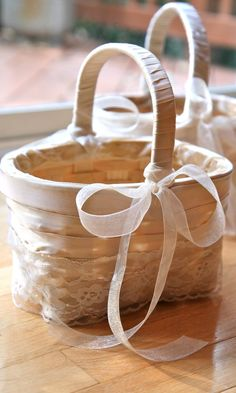"DIY flower girl basket - ""wrapped a bunch of pretty ribbons around a couple of baskets. The end."" - I love it! Simple yet sweet & dainty."
