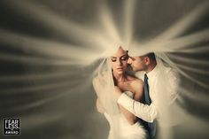 We often see brides and grooms wrapped up in the veil—but those compositions almost always put us outside the fabric. Here, we are wrapped right up with them. Their closed eyes and gentle embrace makes the image feel almost voyeuristic!
