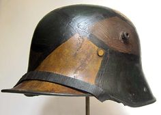 Restored M16 German Helmet in regulation camouflage paint scheme. Points to note are: deep thick paint on sides and worn on top; Rust stains and pot holes dug out and rusted; wrinkled and dried up paint in areas; staining and ageing to paint scheme - not bright and modern; wrinkled, cracked and repaired chinstrap; dark and worn liner.    http://www.warhats.com/ww1-m16-helmet-refurbishment-camo-scheme.html   www.warhats.com