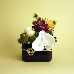 マムやカーネーションなどのプリザーブドフラワーと、蘭や松など、上質なアーティフィシャルフラワーを組み合わせたお正月アレンジ。お年賀としての贈り物にも。※お花はプリザーブドフラワーとアーティフィシャルフラワー(造花)の組み合わせです。※サイズ:直径 約13cm × 高さ 約18cm