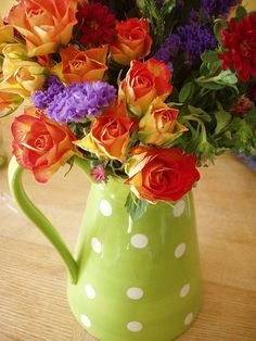 Orange and yellow tea roses in a lime green polka dot pitcher - so colorful! #floral arrangement