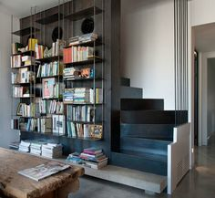 Contemporary bookcase design that forms part of the structure of the stairs in a mid-century modern style apartment in Tel Aviv