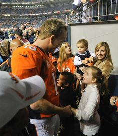 Peyton Manning greets some fans as he heads to the locker room after the win. Broncos vs. Buccaneers 12-2-2012.