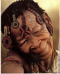 An older San woman wearing beaded tabs or medallions in her hair.