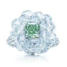 A rare green diamond emerges from tiered white diamonds like a cool summer breeze. Ring with a fancy vivid green diamond and white diamonds in a platinum setting that's almost invisible.