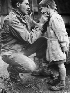 American soldier (Walton Trohon) washes the face of a French orphan