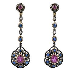 Lovely antique earrings from the end of the 19th Century. Silver topped gold with 2 large pear shaped rubies (approx 1.5 cts each) surrounded by rose diamonds and beautiful sapphires.    Rubies and sapphires are set into gold settings with intricate etched gold work throughout. Circa 1890
