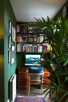 Study nook with book shelves in Small Space Design Ideas. Small green study with framed pictures, bookshelves, house plant and sash window.