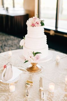 Beautiful classic white wedding cake. Tiered and topped wit pink flowers