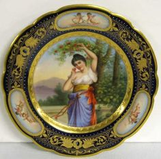 Royal Vienna Porcelain Portrait Plate of a  Woman in a garden picking Apple, with a foliate gilt on cobalt blue border painted with cherubs, circa 1840-1880