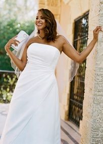 Strapless satin A-line gown with side-draped bodice and asymmetric skirt.   Available in stores and online in White. Ivory available for special order in stores.  Fully lined. Back zip.�Imported Polyester. Dry clean  Add a splash of color by adding a sash at the waist!  Missy: Style T8076. Sizes 0-16.�������