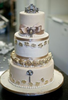 Gold and Eggplant Wedding | tier round white wedding cake with gold roses, pearls and crown on ...