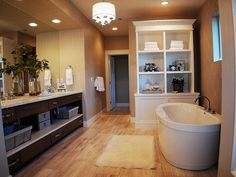 This contemporary bathroom has a freestanding soaking tub, light colored wood floors and a neutral color palette.