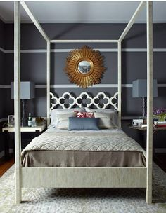 Dior gray bedroom with white chair rail detail, canopy bed with moroccan-style fretwork and sunburst mirror.  Design :: Thom Filicia