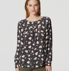 Adorned in florals, this shirred blouse is the sweetest confection. Round neck…