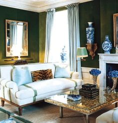 Tory's Burch's emerald velvet clad walls w/ white trim & wainscoting in the living room in her family apartment at the Pierre on the Upper East Side. Aqua silk drapes & pillows, blue & white china, white sofa w/ green trim