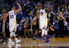 Draymond Green #23 and Stephen Curry #30 of the Golden State Warriors react after the Warriors made a basket against the San Antonio Spurs at ORACLE Arena on January 25, 2016 in Oakland, California.