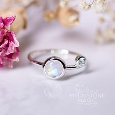 The silver band that holds the Moonstone gem in this Petite Chic Moonstone Ring is polished in 925 Sterling and accompanied by a beautiful Blue Topaz Stone. S