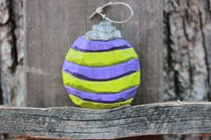 The Ornament- this Christmas tree ornament is 3 inches round and features a purple and lime green green color with a silver top   The Wood- The wood was cut at a saw mill in the flatwoods of East Tennessee in between the Cumberland Plateau and Watts Bar Lake. I literately watch the wood being sliced by my cousin who I went to visit to acquire the wood. Most of my Carvings this winter will be made out of this wood with good memories