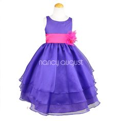 Purple Organza Flower Girl Dress: This elegant purple organza flower girl dress features a sensational sleeveless style with a triple layer skirt. This beautifully simple white organza tea length dress comes with a adjustable sash tie in the back. Like many of our special occasion dresses, it is versatile and can be used as a flower girl dress, pageant dress, or even as a first communion dress.