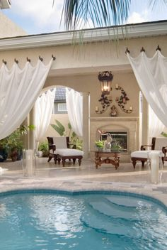 Love the white drapes along side the pool patio -  and the fireplace.