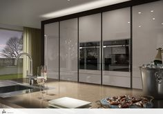 The large bank of larder doors are great for essential kitchen storage, keeping the high gloss kitchen clutter free. Kitchen layout idea by http://setvisionspix.co.uk/