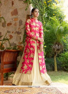 Bring out the true diva in you and reinvent your true self. Make the heads turn as soon as you dress up in this kind of a lovely hot pink and beige net, jacquard and georgette a line lehenga choli. Yo...