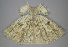 Title: Child's Dress Embroidered with a Plant Motif Place of creation: Germany or Italy Date: Late 17th - Early 18th century Material: silk (ground), golden, silver and silk threads Technique: embroidery in satin stitch, patterned golden and raised laid stitch technique Inventory Number: Т-3900