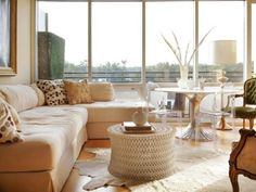 This open concept living room, dining room combination makes the most of the abundant natural light with a neutral palette. Clear chairs and a small metallic pedestal table provide the function of a dining space without blocking the view.