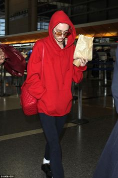 Jet-setter: Lily-Rose Depp, 16, was back at LAX, Los Angeles to jet off to another international destination on Sunday - but she kept a low profile in a bright red sweater worn with the hood up and sunglasses