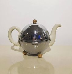"""Antique Original D.R.P. Art Deco Bauhaus Teapot Coffee Pot Bauscher Weiden  Art Deco Vintage Teapot  Size: 11"""" x 6"""" x 7.5"""" / 4 cup   Brand: Bauscher Weiden DRP / Quality Ware . Signed , stamped on base.  Characteristics:: beautiful Art Deco style teapot. White color. Heavy duty porcelain. Split in spout for good pour and large D handle. Outer shell silver colored metal with white ball lid and feet. Insulated pads intact and in good condition.   Condition::  teapot excellent conditions, no…"""