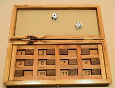 This is our take on the classic pub game called Shut the Box. The box is crafted from hickory, with walnut sliders, and is designed to be