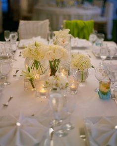 Small, clear vases are set on the reception tables, each containing a different type of white flower.