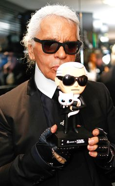 Karl Lagerfeld, in black wayfarer-inspired shades, showed off a bobble head doll of himself at his new store in Munich, Germany! We love that the doll is rockin' sunnies too!