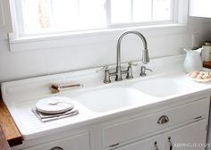 Keeping It Cozy: Our Farmhouse Kitchen with many links including one that talks about refinishing the iron farmhouse sink.