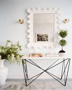 A minimalist-modern console paired with a floor vase and a large mirror with a scalloped frame.