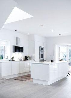 cocina abierta, estilo moderno, muebles lacados en blanco sin tiradores, isla con fregadero, campana decorativa extraplana, suelo parquet