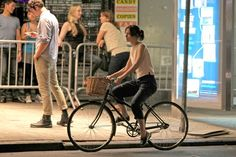 """Keira Knightley Photos Photos - Keira Knightley rides a bike on the set of her latest film, """"Can A Song Save Your Life?"""" in NYC. The actress wears a billowy white top and navy blue capri pants as she bikes around and then stows her bike in a bike rack. - Keira Knightley on the Set of 'Can a Song Save Your Life'"""