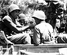 American soldier lighting cigarette of a Japanese-American soldier, both of the US Fifth Army, near Livorno, Italy, 25 Jul 1944.  (Source: Hawaii War Records Depository)