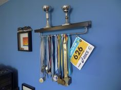 Make medal hanger using Ikea Ribba picture ledge and BYGEL rail.